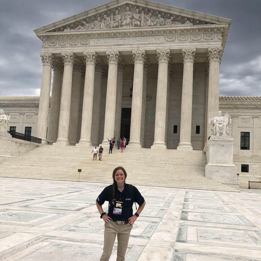 Sydney Aalbers stands in front of the Supreme Court's facade.