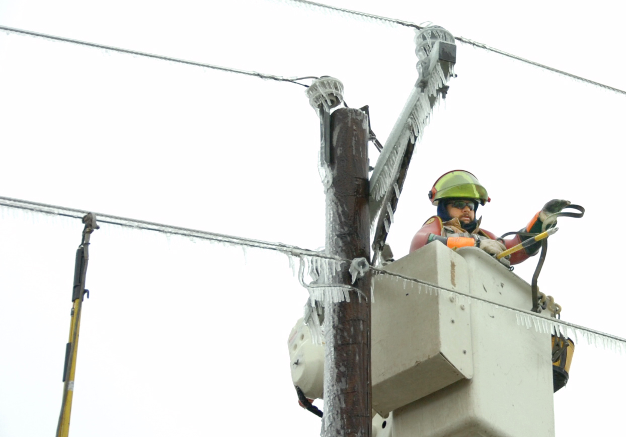 Lineman on icy pole